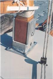 "The tabernacle was welded up from ½"" aluminum that is through bolted astride a double thick (one inch) bulkhead. The mast pivots on the upper bolt and the lower bolt is inserted and fastened once the mast is standing. The 1/8"" ss shrouds are attached to galvanized chain plates with turnbuckles and are left in place when the mast is lowered. The forestay attached easily to the bowsprit bracket via a pelican hook. The gaff bridle is also made of 1/8"" ss wire rope. Setting up is fairly simple – the mast is manually hinged into place, the lower tabernacle bolt inserted (temporary hold). The forestay in fastened via the pelican hook. Boom and gaff jaws and two sail luff ties fastened to mast and hoist away. In the lowered position the mast, boom and gaff with sail attached, and mizzen rest in holding fixture on the cabin top and a crutch in the cockpit."