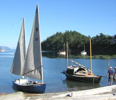 I don't have a picture of Blew-by-You sailing, but here she is at the beach, beside Lynn Watson's modified Drascombe Peterboat,Katie Mae.